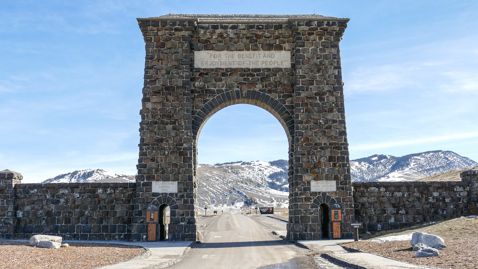 a stone arch over a driving path leading to snow covered mountains