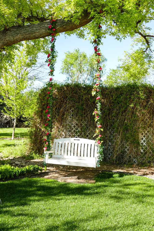 A white swing hangs from a tree in the garden. Flowers are intertwined in the chains hanging down from the tree with a carpet of grass underneath the swing.