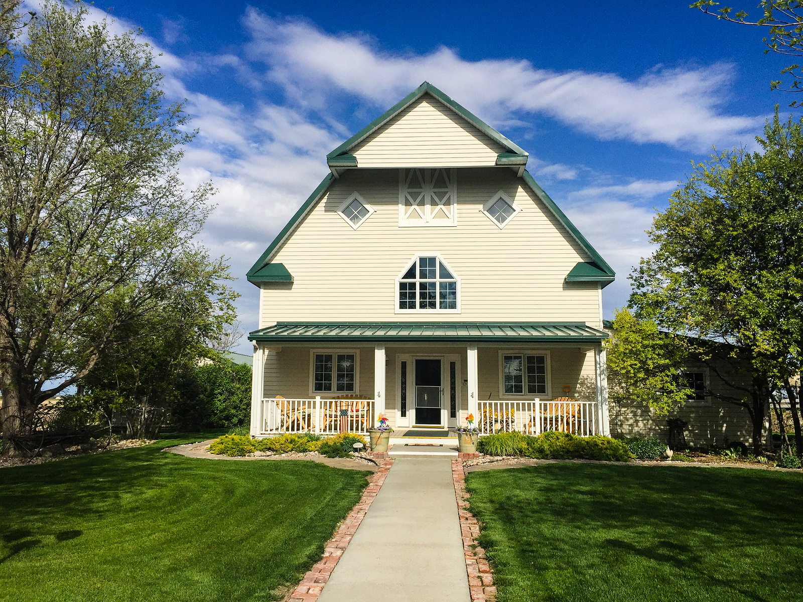Cream colored barn accented by dark green roof and trim, green lawn and white clouds in a blue sky at Barn Anew.