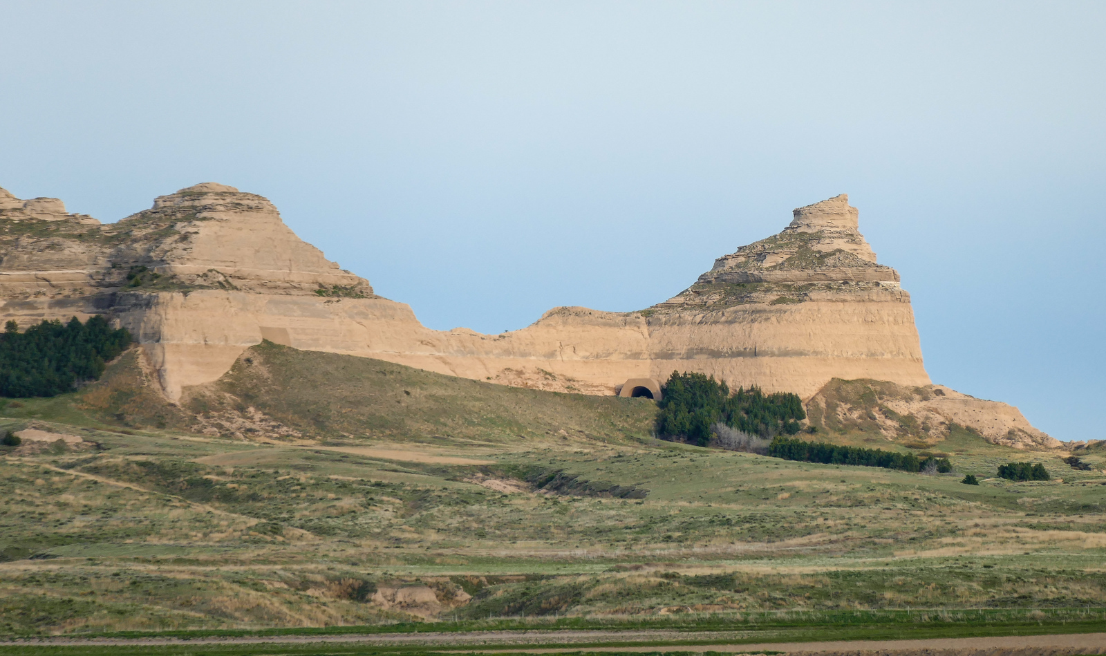 Beige bluffs surrounded by green grass and a blue sky at Scott Bluff National Monument.