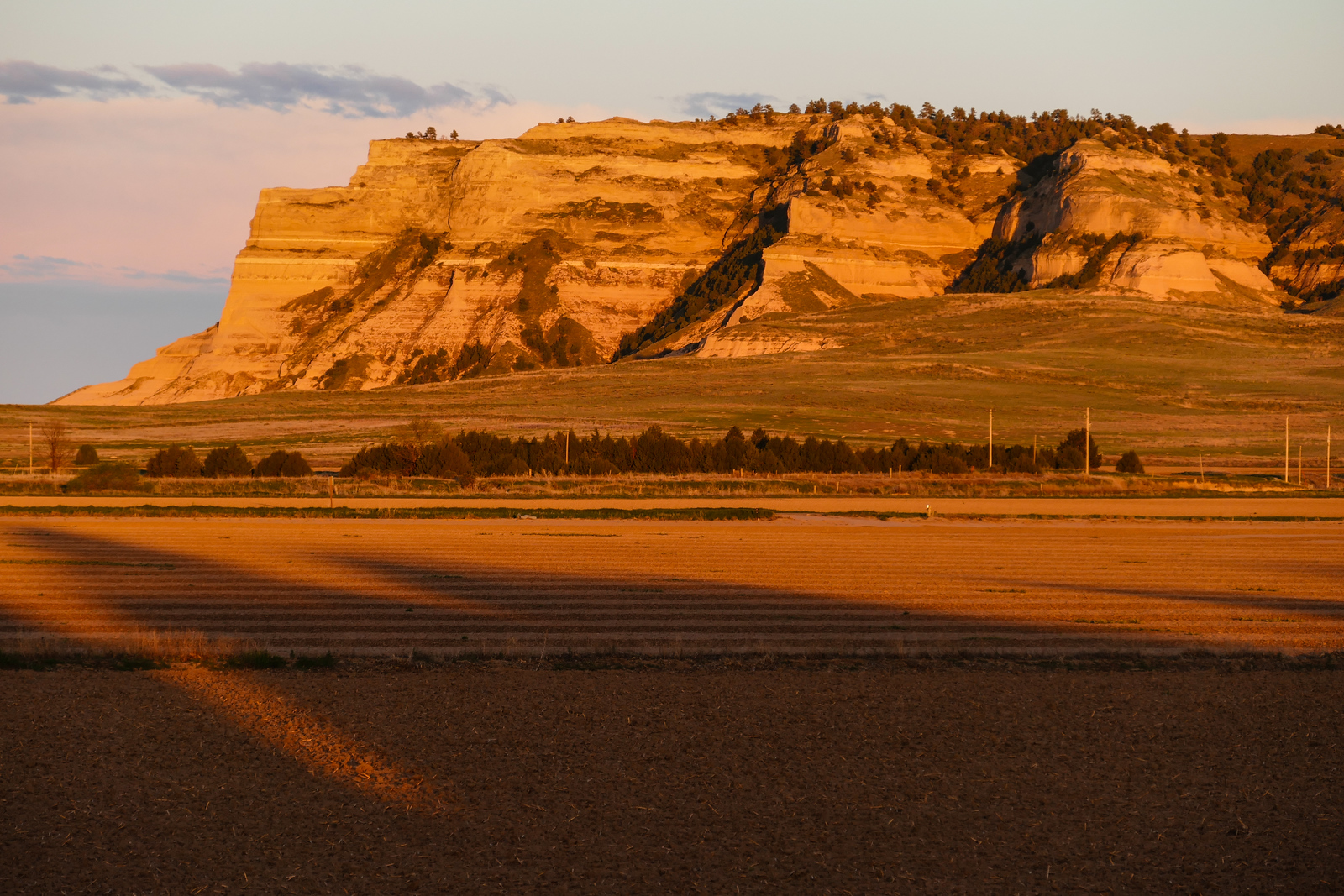 A sunset paints the bluffs orange at Scotts Bluff National Monument.