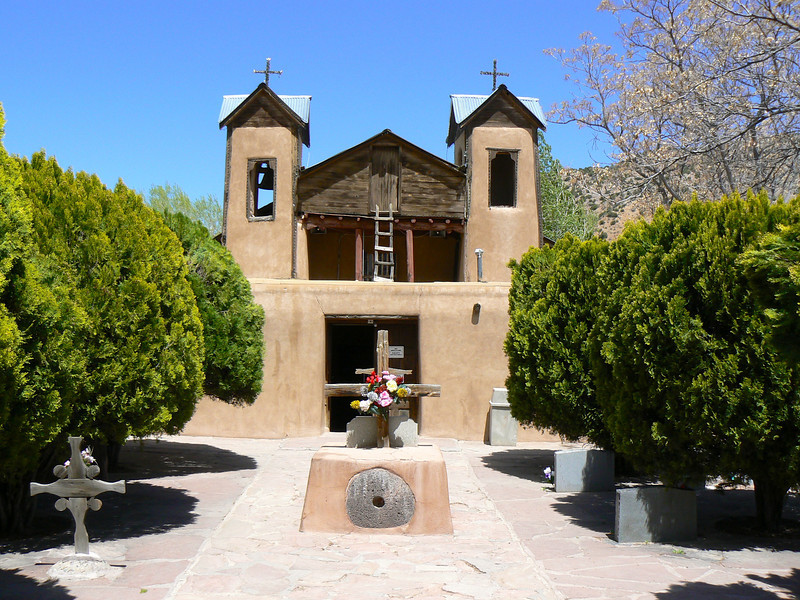 An adobe church surrounded by green landscape.