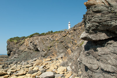 Lobster Cove head lighthouse as seen from rocky shores of Gros Morne National Park