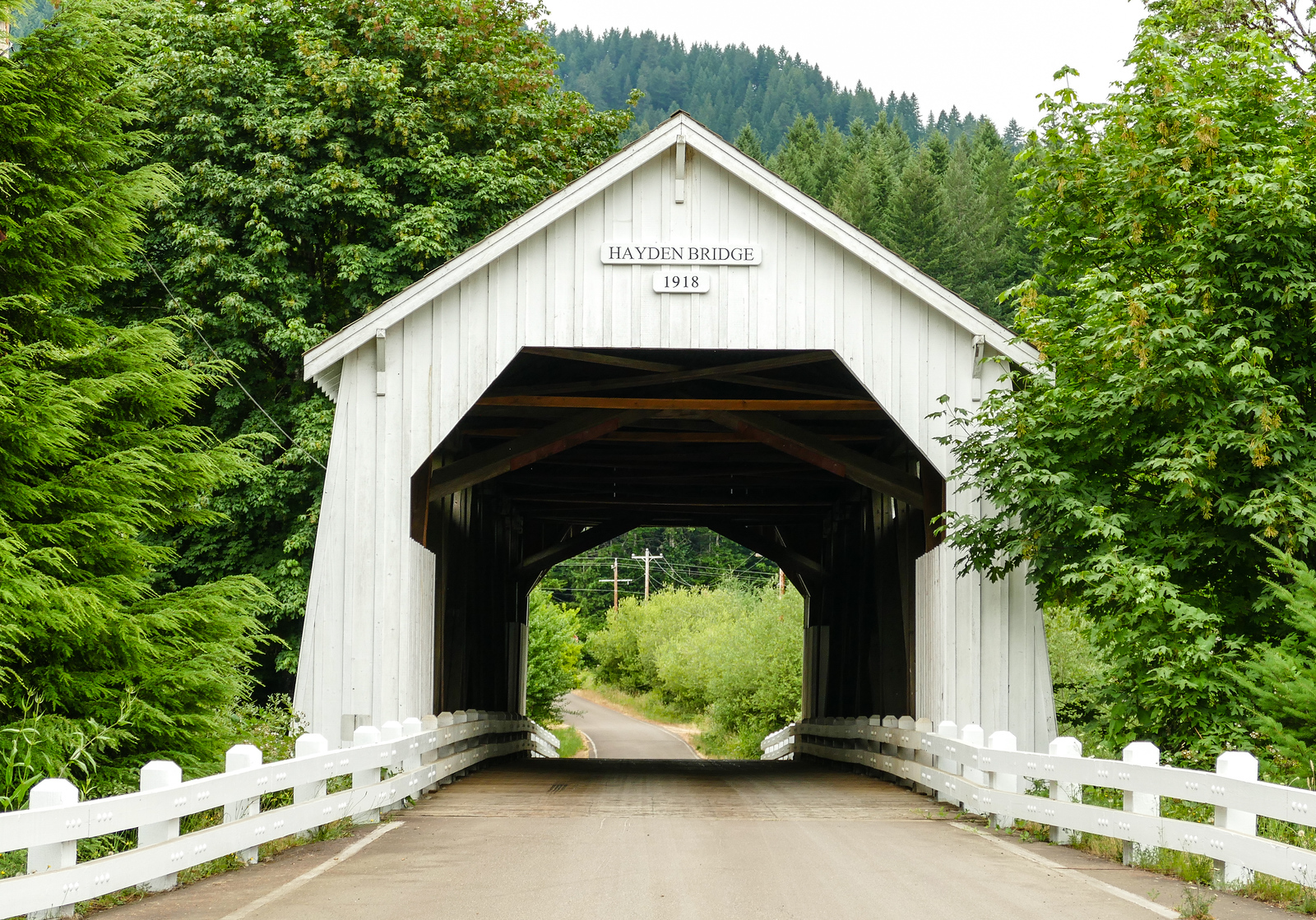 A white covered bridge surrounded by green trees in Oregon.