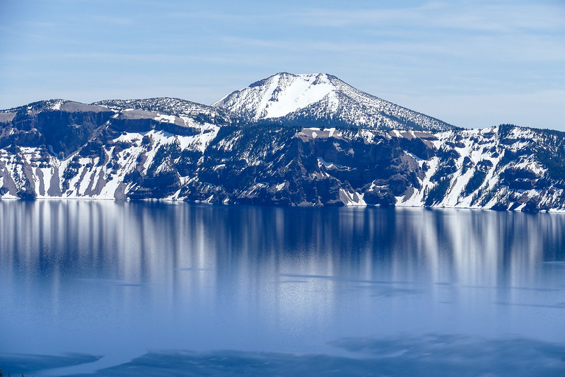 Snow-capped mountains reflect in the blue lake on a spring trip to Crater Lake National Park