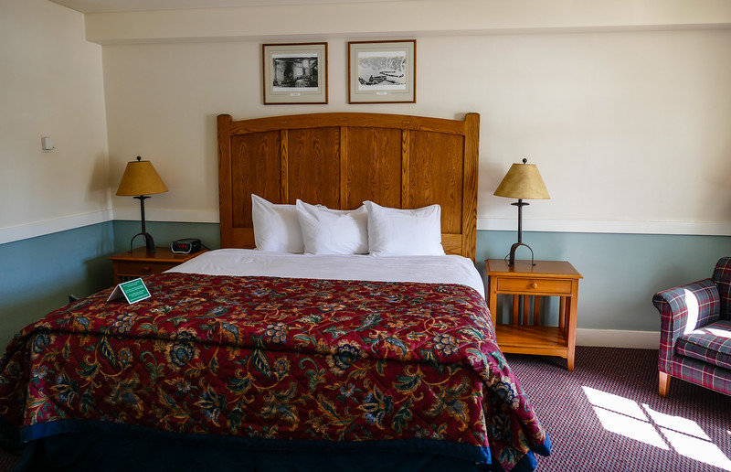 Photo of a Crater Lake Lodge room shows a bed with wood headboard, night stands and burgundy bedspread.
