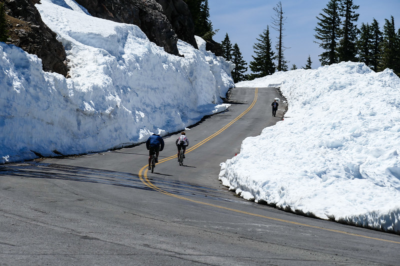 Bicyclists ride the cleared Rim Drive in between huge snow banks.