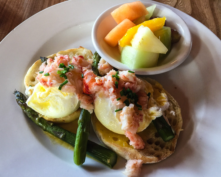 Crab benedict served with fruit and asparagus on a white plate.