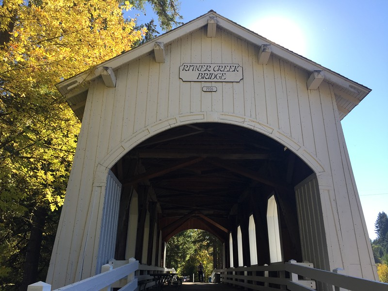Covered bridge surrounded by gold autumn leaves and a sunny blue sky.
