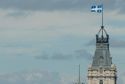 Fflag of the province of Quebec waving over the Parliament Building in Quebec City, Quebec