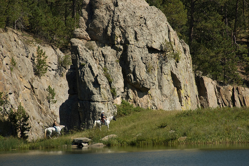Horse back riders near a wall of mountain in Black Hills, South Dakota