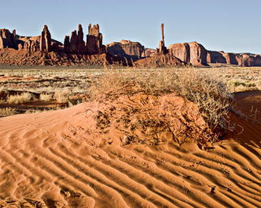 The sand dunes in Monument Valley facing the dancers and totem pole in the morning sun.