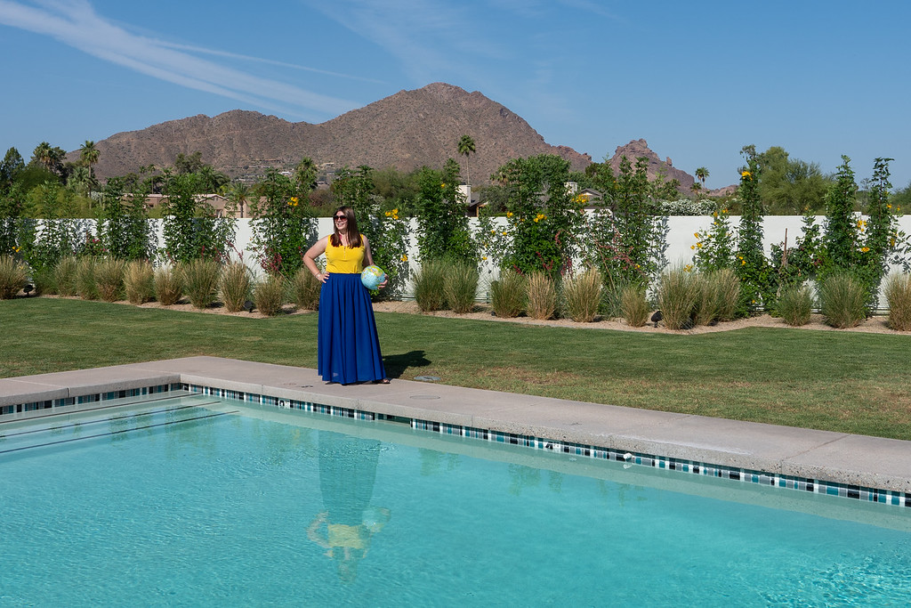 Amanda standing by a pool with Camelback Mountain in the background