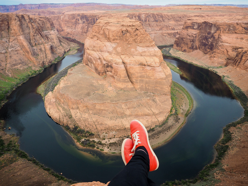 Feet hanging over the edge at Horseshoe Bend in Arizona