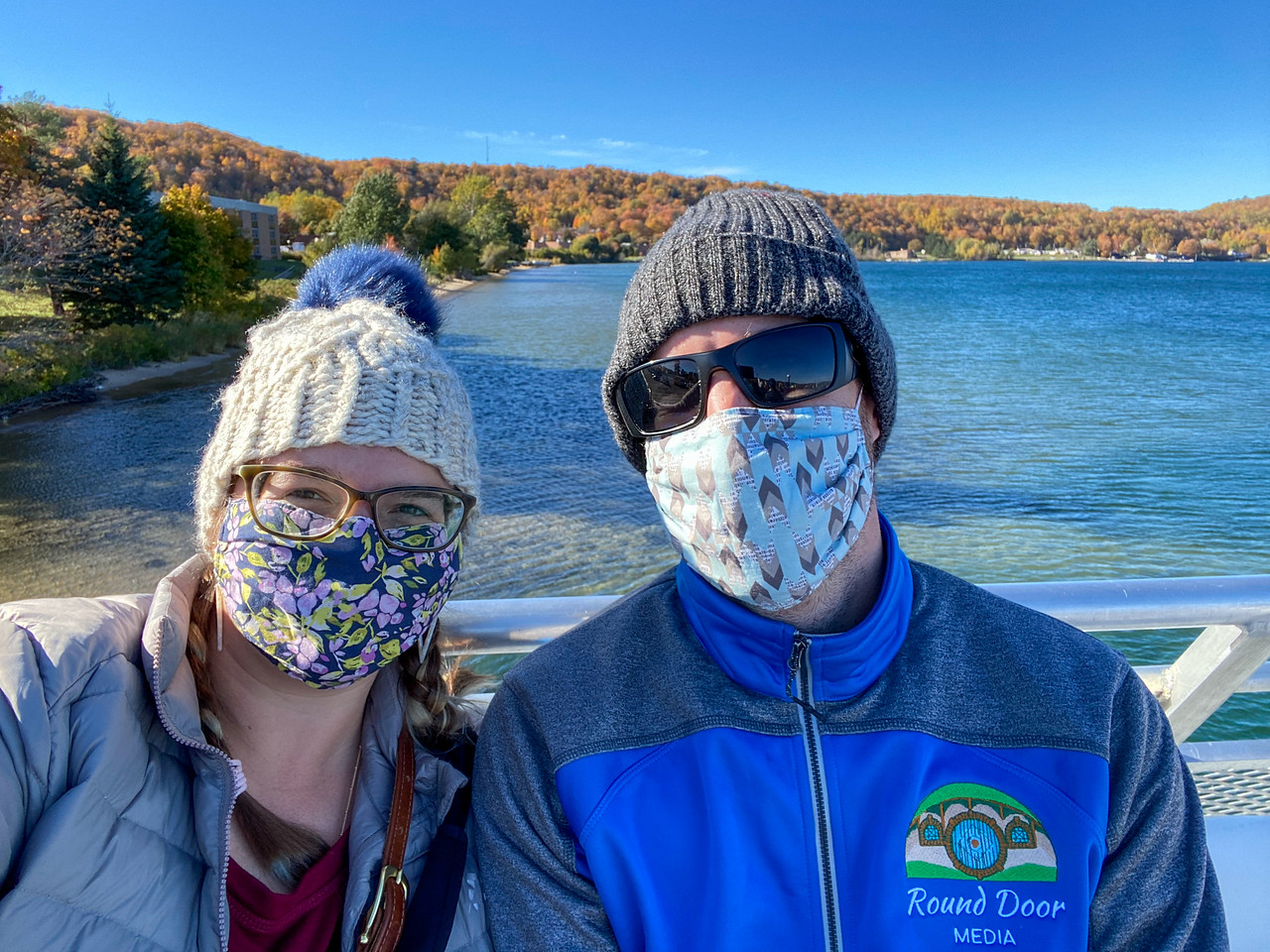 Amanda and Elliot in masks and beanies on a cruise boat