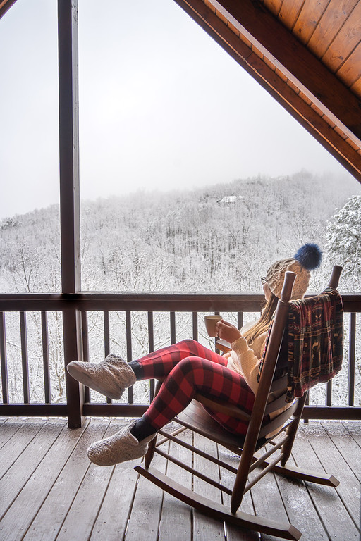 Amanda in a rocking chair looking out at snow