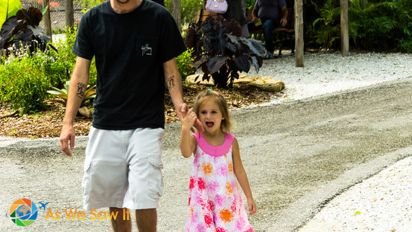 Daddy leading Leia along nice paved paths through Naples Zoo