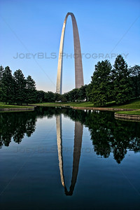 The Gateway Arch in St. Louis stands alongside a calm reflection pond.