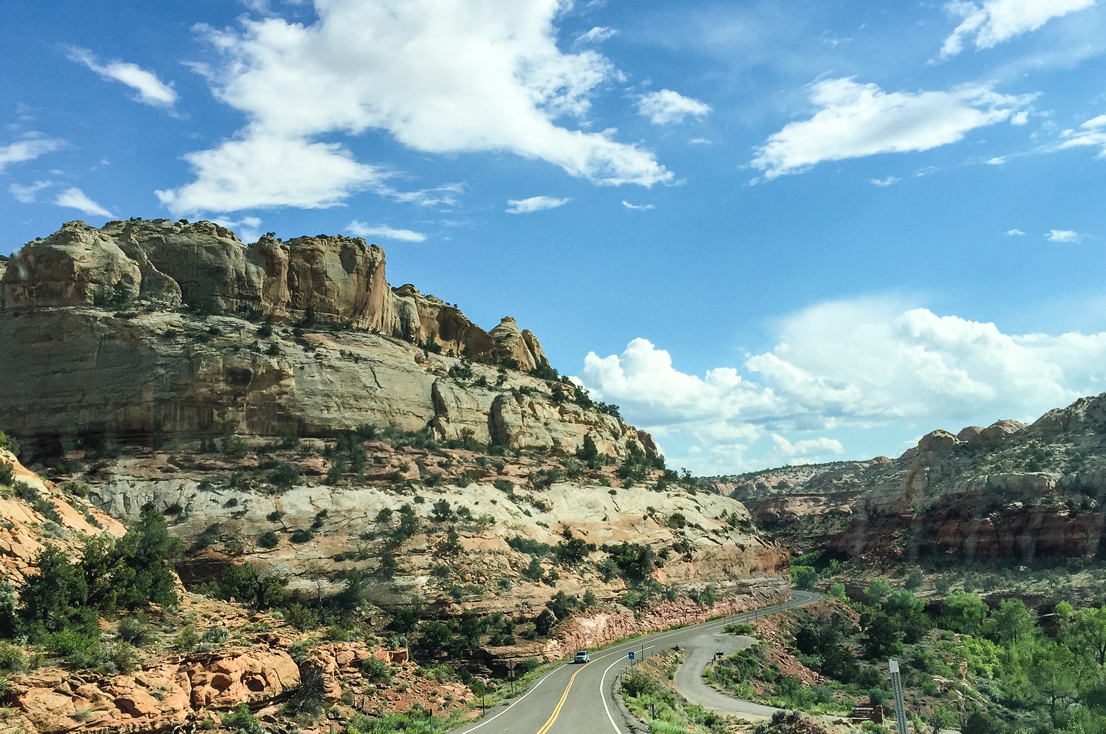 A highway travels through beside pink and beige sandstone hills in Grand Staircase-Escalante.