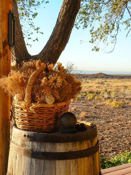 Golden-colored dried flower arrangement sitting in a basket underneath a tree.