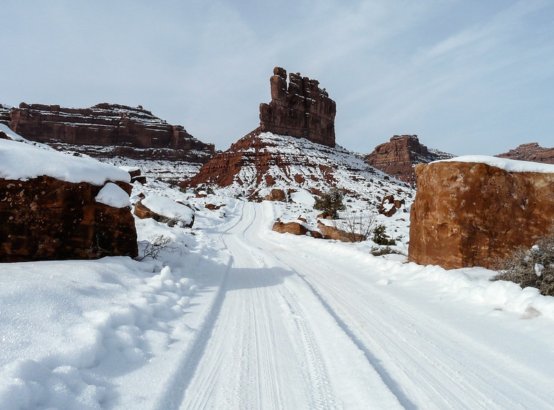 A snowy road winds between red rock buttes