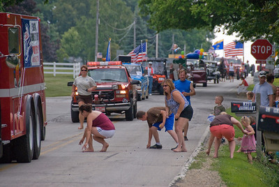 Onlookers picking up coins on the road during Stephensville Parade, Wisconsin