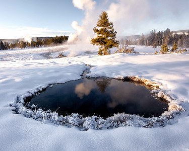 A pool of thermal water reflects the steam from another geyser in upper old faithful basin