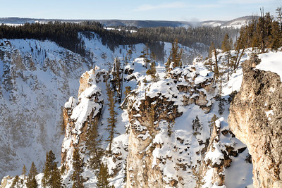 Grand canyon of the yellowstone in winter with the falls behing the rocks.