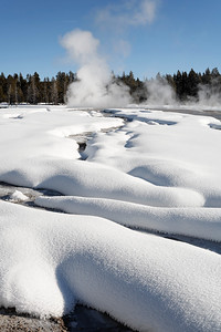 Norris geyser basin in winter.  The hot water makes interesting patterns in the snow.