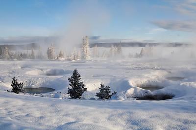 Geothermal pools stay clear of snow while everything else is frozen along the shore of yellowstone lake.