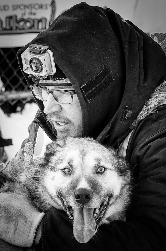 Musher and his sled dog at the start of the 2013 Yukon Quest