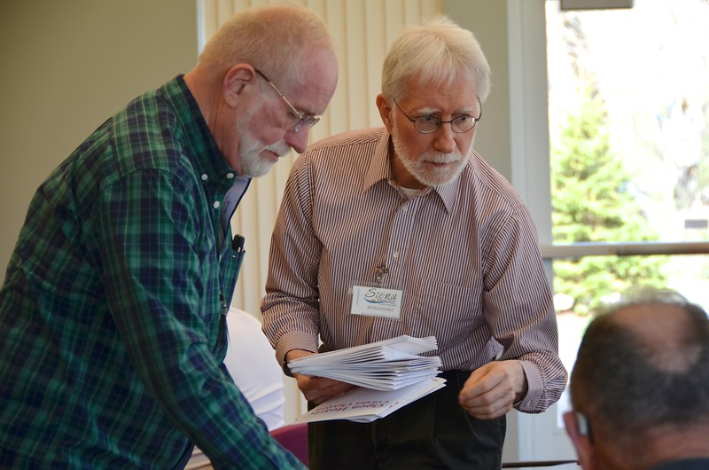 David Schimmel, director of Dehonian Associates and a member of the retreat planning committee, distributes reflection guides.