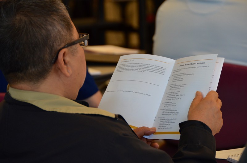 Fr. Vincent reviews the reflection booklet for the day