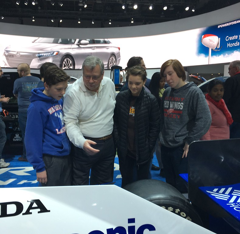 . Wayne Hodges, center, of Lakeville, and a former race car driver explains a few facts about a race car on display at the NAIAS to his grandchildren including Patrick Hodges, far left, Courtney Hodges and Nick Hodges. GINA JOSEPH - THE MACOMB DAILY