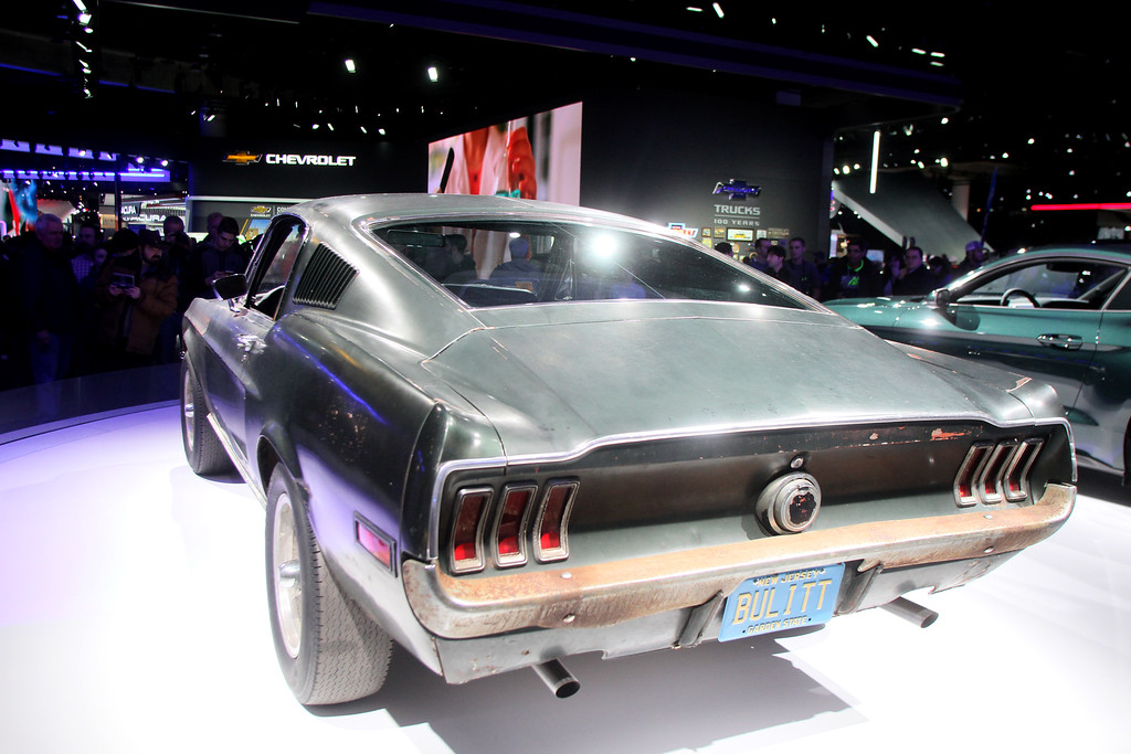""". Despite the new wheels on the show floor, one of the cars people flocked to see was a 50-year-old Mustang GT fastback in need of a paint job. It was one of the original cars used in the 1968 film, \""""Bullitt,\"""" starring Steve McQueen. Shining brightly next to it is the new Mustang, inspired by the \""""Bullitt.\"""""""