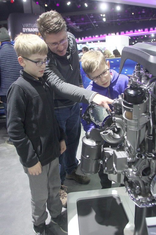 . Robert Horvatich shows his son\'s Gavun and Jake a model engine that\'s in his vehical