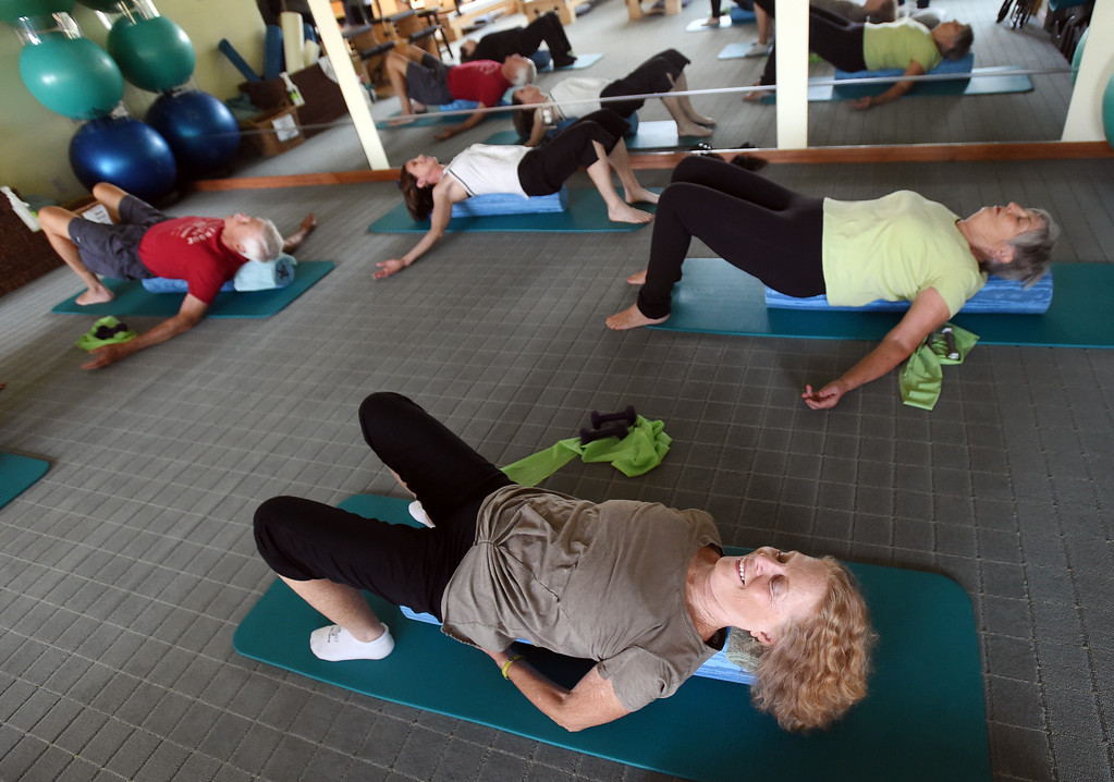. Shirl Linderberg, bottom, does the North Boulder Pilates class with John Farnbach, top left, instructor, Michelle Harris, and Connie Farnbach.  Cliff Grassmick  Staff Photographer  August 7, 2018