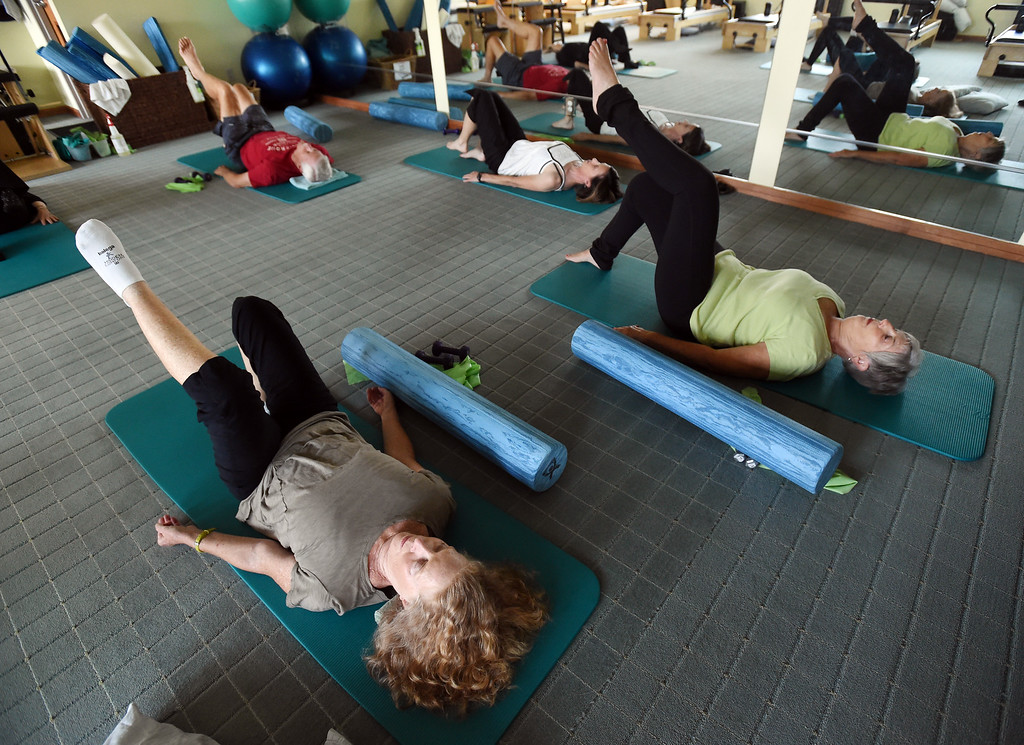 . Shirl Linderberg, bottom left, does the North Boulder Pilates class with John Farnbach, top left, instructor, Michelle Harris, and Connie Farnbach.  Cliff Grassmick  Staff Photographer  August 7, 2018