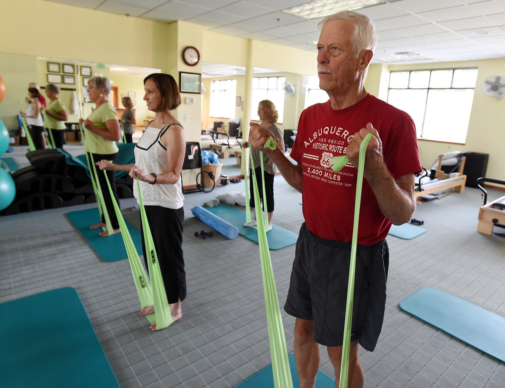 . John Farnbach, right, works out during the North Boulder Pilates class. taught by Michelle Harris, left.  Cliff Grassmick  Staff Photographer  August 7, 2018