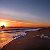 Man with surfboard on the beautiful sunrise beach.