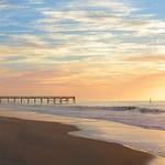 Sunrise over pier on Atlantic ocean.