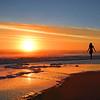 Woman relaxing on the beach enjoying beautiful sunrise,
