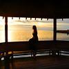 Girl  enjoying  beautiful view of sunset on the lake .