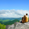 Couple siting on top of mountain.