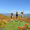 People with hands up jumping  and having fun on the top of  mountain. Family weekend autumn trip, looking at  beautiful fall mountain view.Blue Ridge Parkway. Close to Asheville, North Carolina, USA.