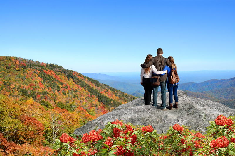Family enjoying beautiful autumn view on  hiking trip in mountains.
