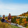 Girl standing on a mountain looking at beautiful autumn mountain landscape during her hiking trip. Linn Cove Viaduct. Close to Blowing Rock, Blue Ridge Parkway, North Carolina, USA.