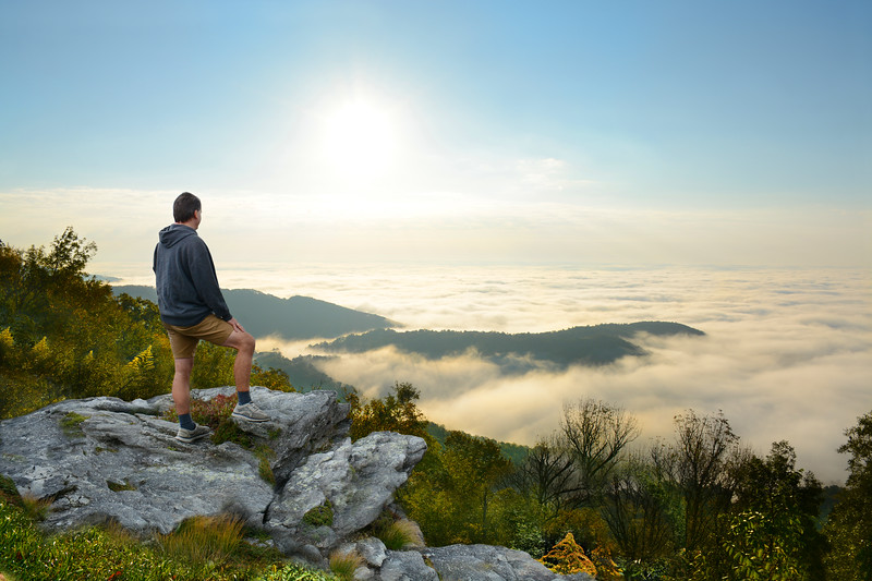 Man standing on a top of the mountain enjoying  beautiful foggy mountain view, during his  autumn hiking trip. Close to Blowing Rock, Blue Ridge Parkway, North Carolina, USA.