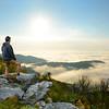 Man standing on a top of the mountain enjoying  beautiful foggy mountain view, during his  autumn hiking trip. Close to Blowing Rock, Blue Ridge Parkway, North Carolina, USA.