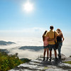People on hiking trip in mountains. Father with arms around his family enjoying time on top of  mountain looking at beautiful scenery..Blue Ridge Parkway, close to Blowing